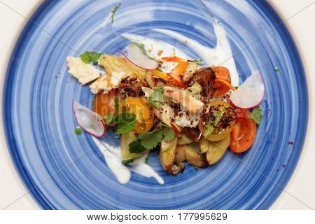 Chicken salad with vegetables on blue plate shot from above
