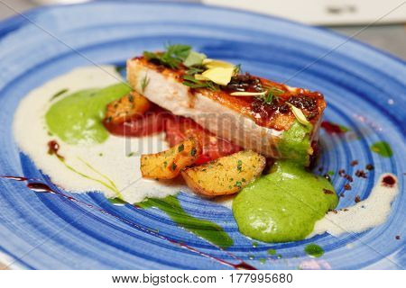 Fried chicken fillet with potatoes on blue porcelain plate