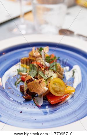 Chicken salad with vegetables on blue plate, restaurant table setting