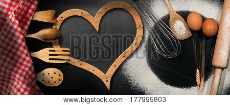Baking background with empty blackboard in the shape of a heart on a black table with wooden kitchen utensils flour ears of wheat and a checkered tablecloth