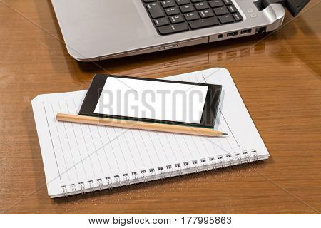 Blank notebook pencil with smartphones and laptop on wooden table
