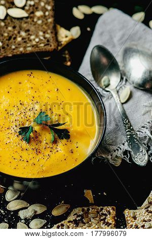 Pumpkin soup with cream and parsley on rustic background Top view