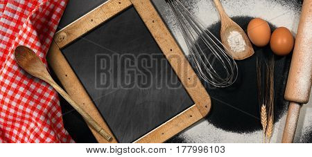 Baking background with empty blackboard on a black table with Rolling pin whisk eggs spoons ears of wheat and a red and white checkered tablecloth