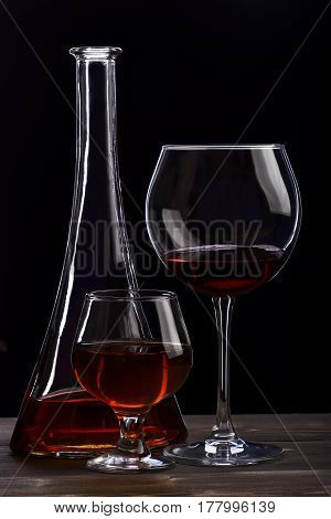 set of glasses and carafe with cognac or whiskey on wooden table black background side view