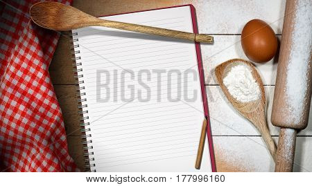 Baking background with empty notebook for recipes or ingredients list on a wooden table with flour egg rolling pin spoons and red and white checkered tablecloth