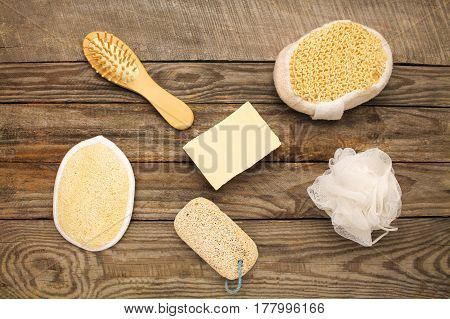 Hygiene products: soap,comb, sponge, pumice stone on old wooden background. Top view.