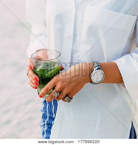 Woman hands with green cocktail in glass