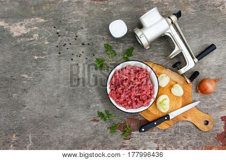 Grinder, meat, onions, black pepper, salt, parsley on the table. Top view.