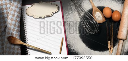 Baking background with empty notebook and label for recipes or ingredients list on a black table with flour eggs whisk rolling pin spoons and a checkered tablecloth