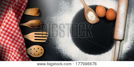 Baking background - Rolling pin and wooden kitchen utensils with flour and eggs on a black table with a round copy space and red and white checkered tablecloth