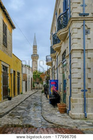 Cami Kebir Mosque. Street scene with Mosque at the end.  Shows the minaret and a typical narrow street scene in the old town of Limassol.