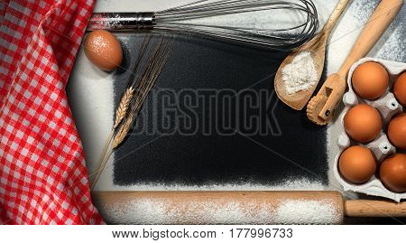 Baking background - Kitchen utensils ears of wheat eggs checkered tablecloth and flour with rectangular copy space on a black table