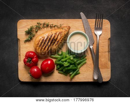 Marinated grilled healthy chicken breast served with green beans and, white sauce and fresh tomatoes on a wooden board, top view