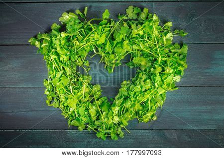 A heart shaped wreath of cilantro leaves, shot from above on a dark wooden background texture with a place for text