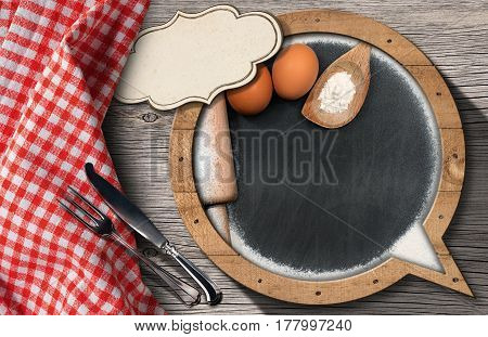 Blackboard with copy space in the shape of speech bubble with flour eggs rolling pin spoon and silver cutlery on a wooden table with a checkered tablecloth