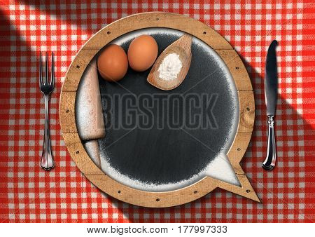 Blackboard with copy space in the shape of speech bubble with flour eggs rolling pin spoon and silver cutlery on a table with a checkered tablecloth