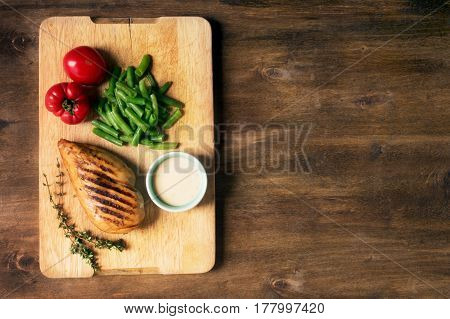 Marinated grilled healthy chicken breast served with green beans and, white sauce and fresh tomatoes on a wooden board, top view. Horizontal orientation
