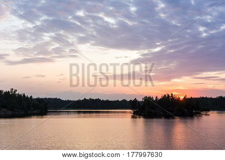 Dramatic summer sunset with clouds on a forest lake