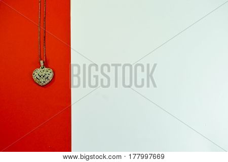 Heart-shaped pendant on a red strip on a white background