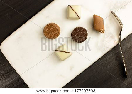 An overhead photo of various artisan chocolate bonbons with a small dessert fork and copy space