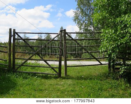 Green grass and a gate, blue sky with clouds