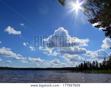 Peaceful lake with blue sky, sunny weather.