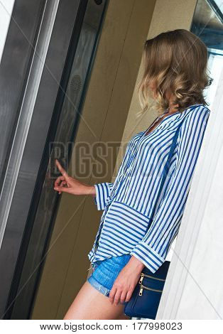 Woman Pressing The Button Inside The Elevator.