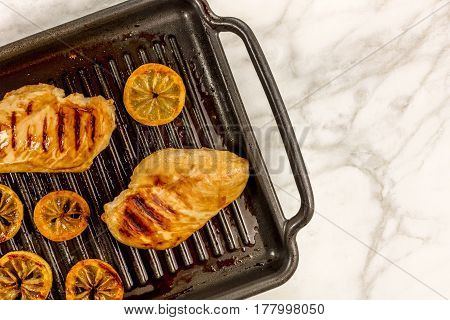 An overhead photo of grilled chicken breasts on the pan, with lemon slices and a place for text