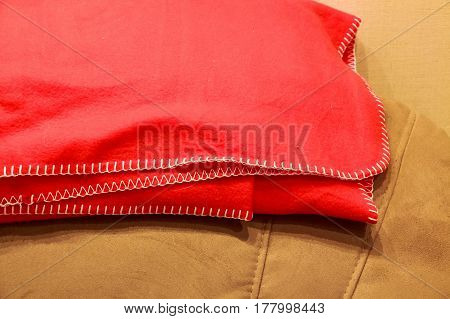 Closeup of folded red fleece plaid on top of sofa