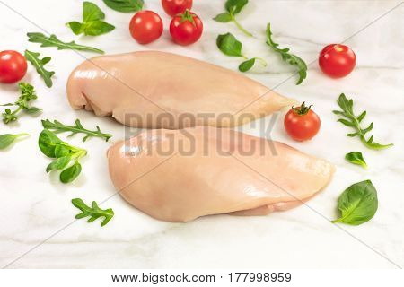 Chicken fillets with cherry tomatoes, fresh herbs including basil leaves, corn salad, and ruccola, on a while marble table with a place for text