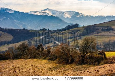 high mountain ridge with snowy peaks. hillside with forest in springtime. road winds through rural fields. Beautiful Carpathian nature. High altitude spectacular view.