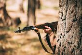 Re-enactor Dressed As Russian Soviet Infantry Soldier Of World War II Hidden With Rifle Weapon In An Ambush Near Tree In Forest. Close Up On Soviet Rifle In Hands poster