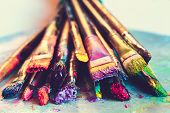 Artist paintbrushes with paint closeup on artistic canvas. Retro toned. Selective focus. poster