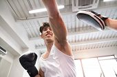 Handsome fit hispanic man in gym boxing with unrecognizable rival poster