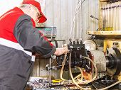 Professional mechanics testing diesel injector in his workshop repair of diesel fuel injectors ustroustvo for the diagnosis of fuel injectors poster
