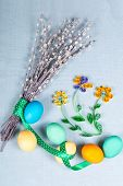 Pussy willow with lovely polka dot ribbon painted eggs and hand made paper flowers on blue fabric tablecloth. Bright Easter still life. Top view. Vertical orientation. poster