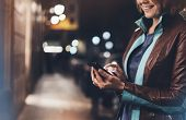 Girl smile pointing finger on screen smart phone on background illumination color light in night atmospheric city hipster using in female hands and text mobile phone mock up glitter street content lifestyle poster