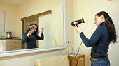 Beautiful brunette woman drying long black silky hair with hairdryer and smartens up in front of mirror in make-up dressing room. poster