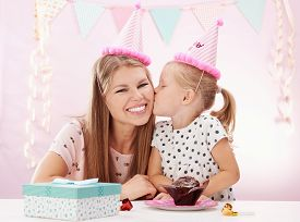 Portrait of cute girl kissing her mum for birthday gift. Concept of birthday party celebration and fun.