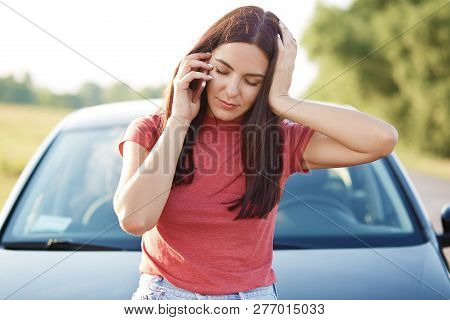 Tired European Woman With Long Hair Has Telephone Conversation Via Mobile Phone, Feels Tired After R
