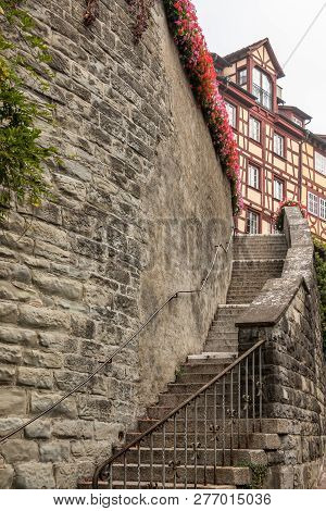 High Stone Wall With A Long Stairway To Some Old Medieval Houses