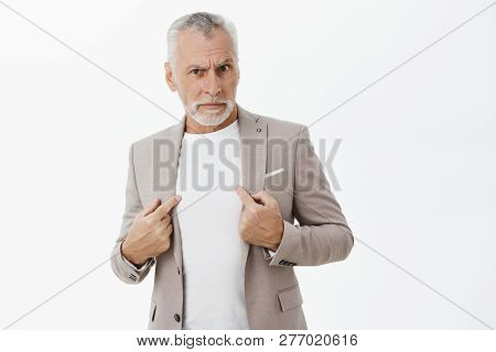 Portrait of senior man being accused in commiting crime standing insulted and intense pointing at himself with serious displeased and offended expression asking question at camera over gray wall poster