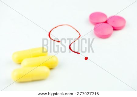 The Concept Of Choosing A Drug Or Method Of Treatment. Yellow And Pink Pills On A White Background W