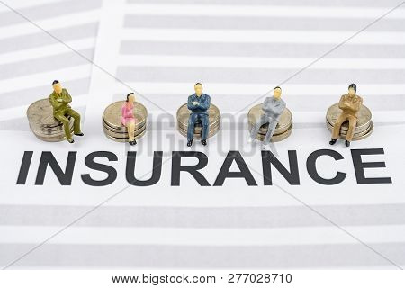 The Concept Of Corporate Health Insurance From The Employer. People Figurines Sit On Piles Of Coins