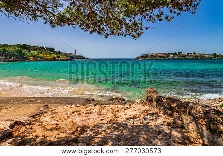 Idyllic Beach On Mallorca Island, At The Bay In Porto Colom With View Of The Lighthouse