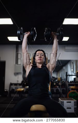 fitness girl trains with dumbbells in the gym. Pumps the deltoid muscles poster
