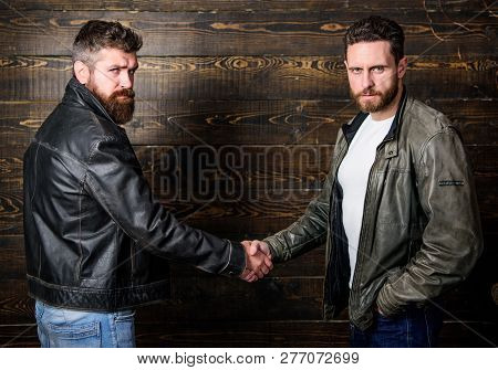 Male Friendship Concept. Brutal Bearded Men Wear Leather Jackets Shaking Hands. Real Men And Brother