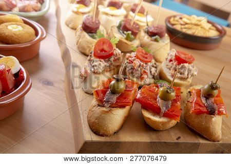 Small Appetizers On Skewer With Cheese, Olives And Sausage. Tapas Or Antipasto Food