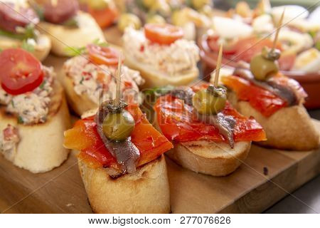 Small Appetizers On Skewer With Cheese, Olives And Anchovy. Tapas Or Antipasto Food
