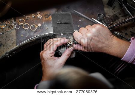 Jeweler polishes a gold ring on an old workbench in an authentic jewelry workshop poster